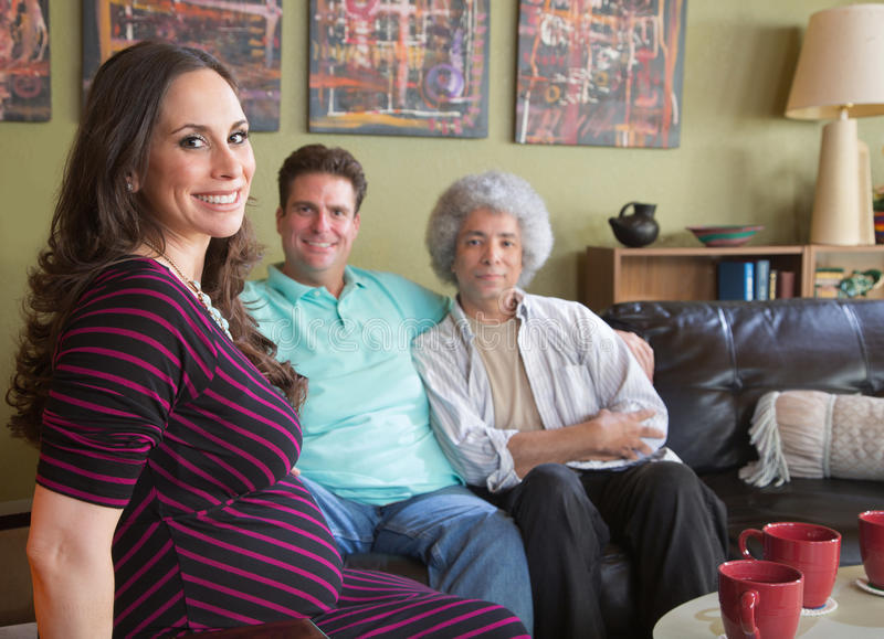 Pregnant Surrogate Mom with Couple. Happy pregnant surrogate female with mixed gay couple stock images