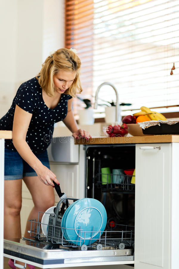 Pregnant wife doing house chores. In kitchen with the help of a machine royalty free stock photos