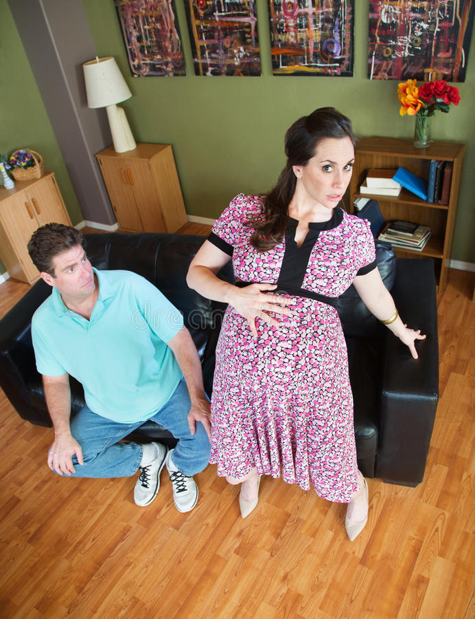 Pregnant Wife Getting Up. Husband watching awkward pregnant wife getting up from sofa stock photography