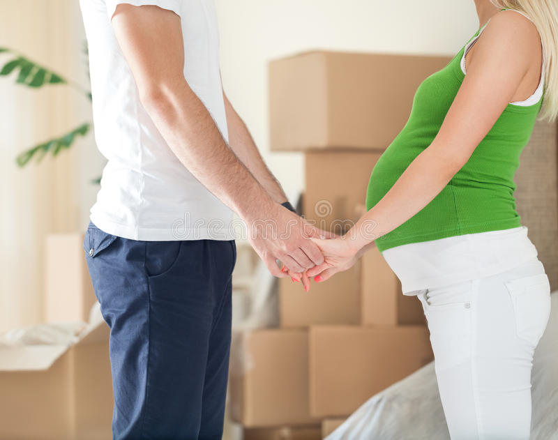 Pregnant wife holding hands of her husband in new home stock image