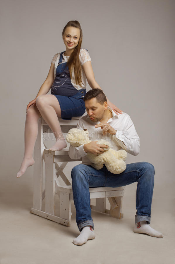 Pregnant wife with the husband who holds Teddybear stock photo