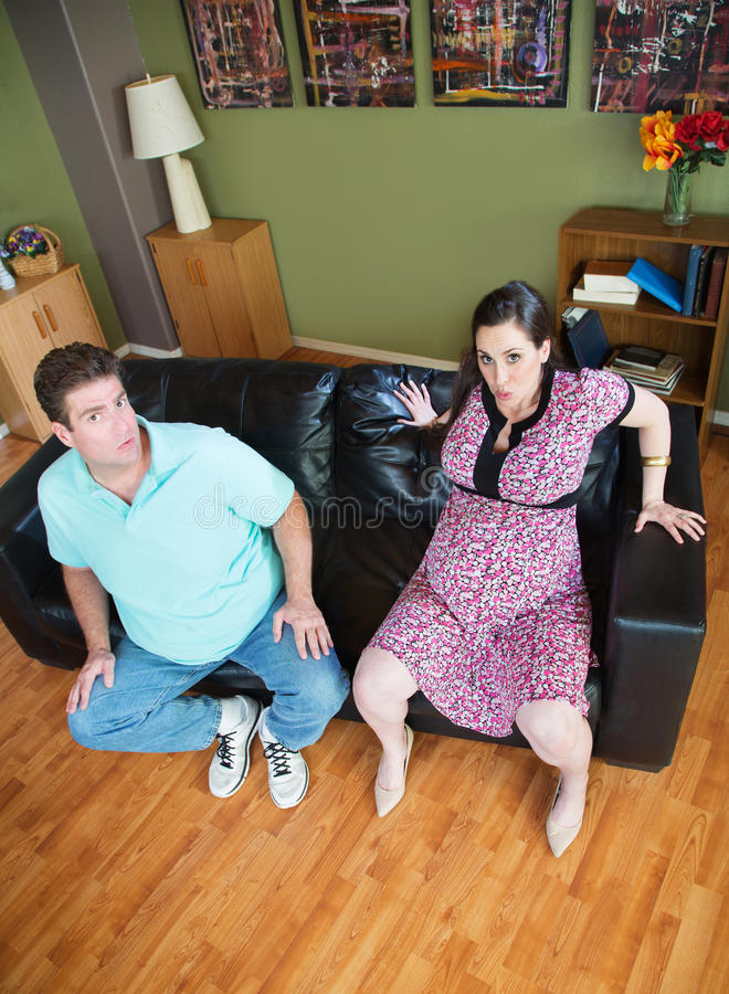 Pregnant Wife Stuck in Sofa. Man with pregnant women stuck in sofa royalty free stock image