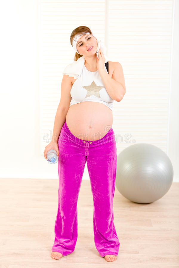 Pregnant Wiping Face With Towel After Exercising Stock Photo