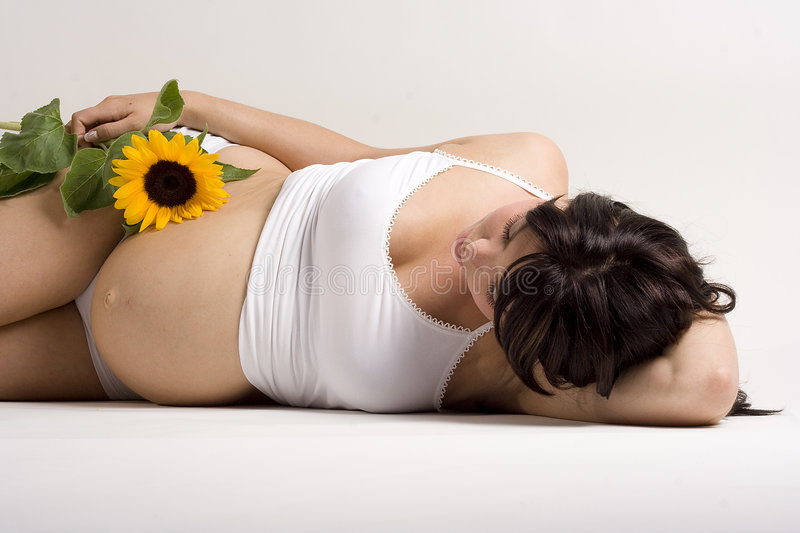 Pregnant woman. A pregnant woman lying on the floor with a sun flower royalty free stock photos