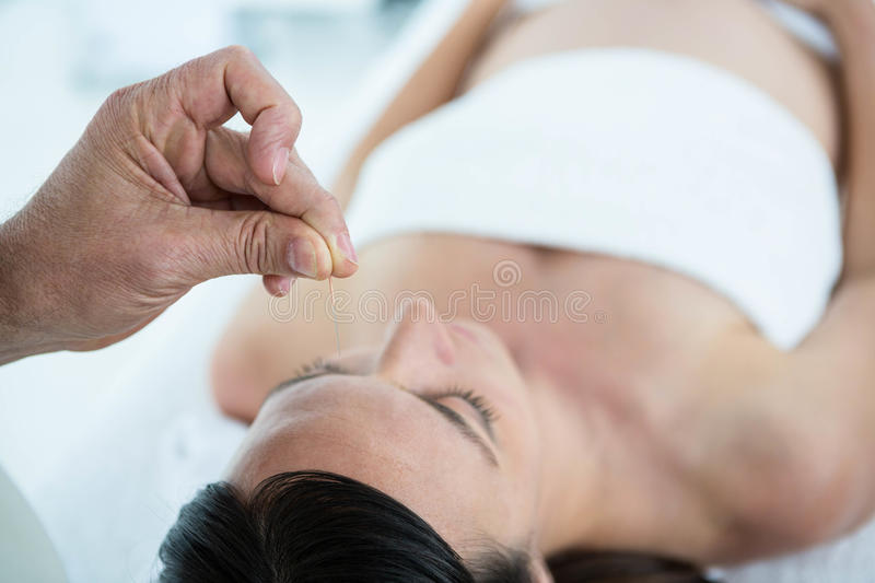 Pregnant woman in an acupuncture therapy royalty free stock image