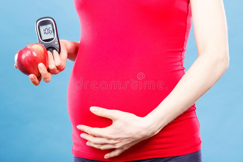 Pregnant woman with apple and glucose meter with good result sugar level, diabetes and nutrition during pregnancy. Pregnant woman holding fresh apple and royalty free stock photos