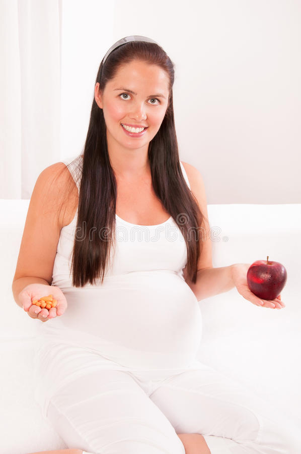 Pregnant woman with an apple in one hand and vitamins stock photos