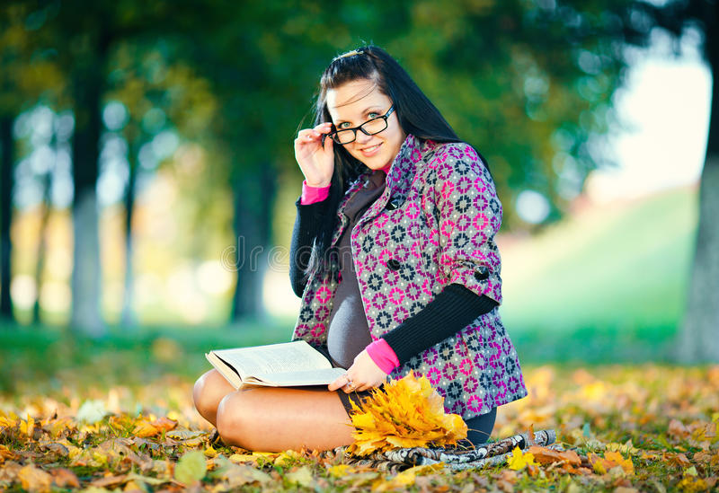 Pregnant woman in autumn park. Reading book stock photography