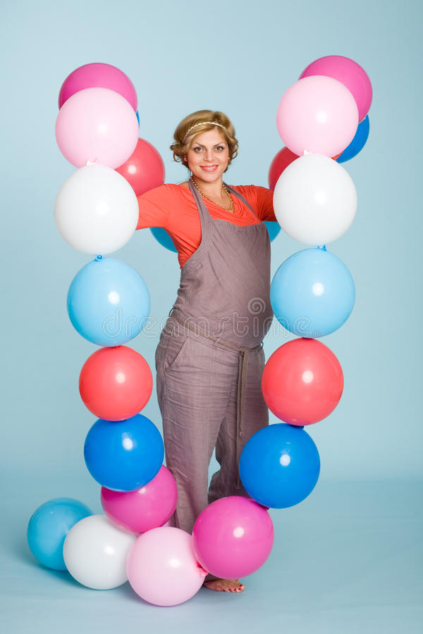 Pregnant woman with balloons. Joyful pregnant woman with balloons royalty free stock photos