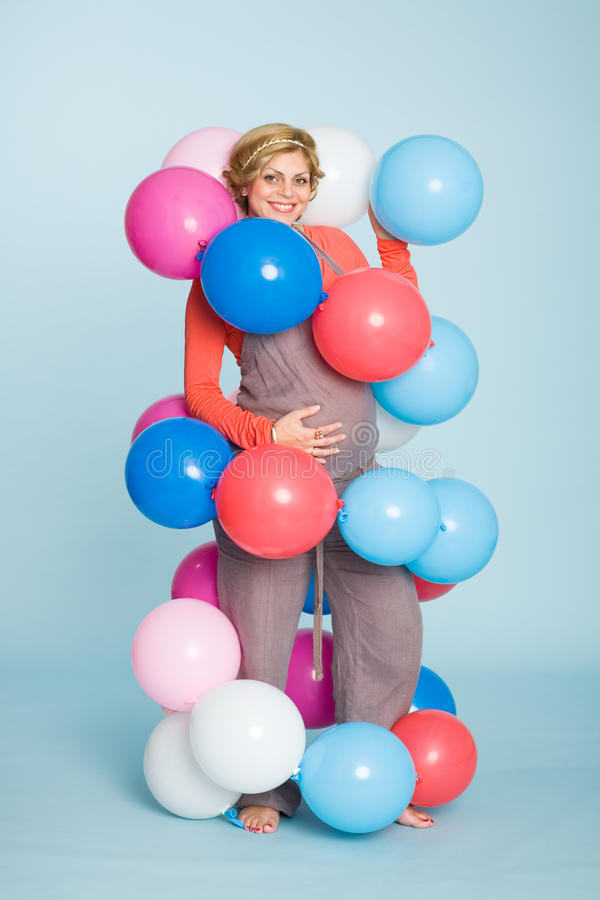 Pregnant woman with balloons. Joyful pregnant woman with balloons stock images