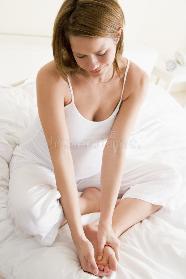Pregnant woman on bed smiling and rubbing feet stock images