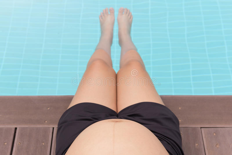 Pregnant woman belly with legs in swimming pool. royalty free stock photography