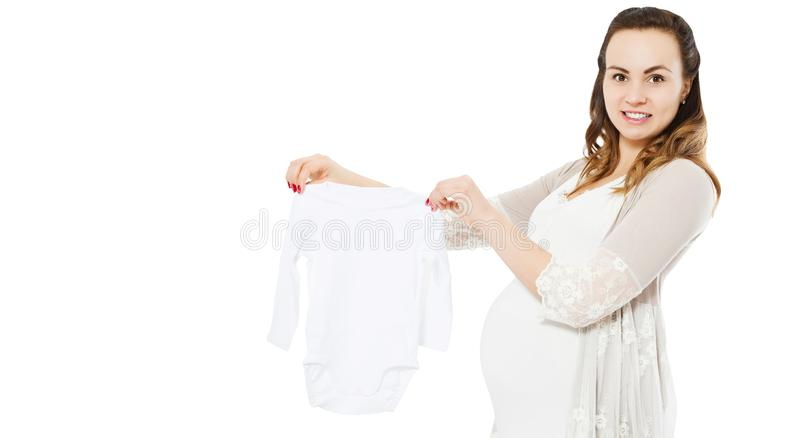Pregnant woman with belly shows baby clothes on white royalty free stock images