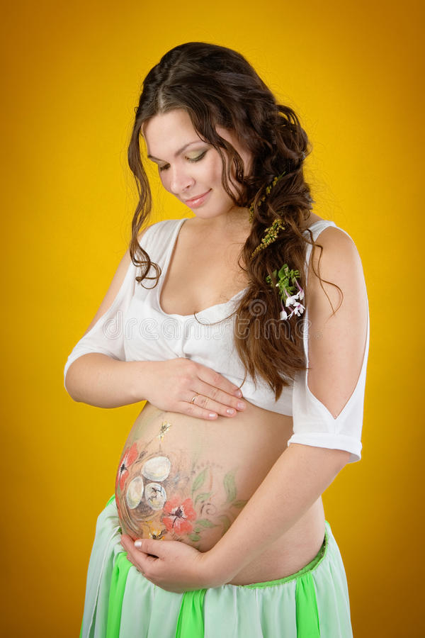 Pregnant woman with body arti painting on her belly royalty free stock photos