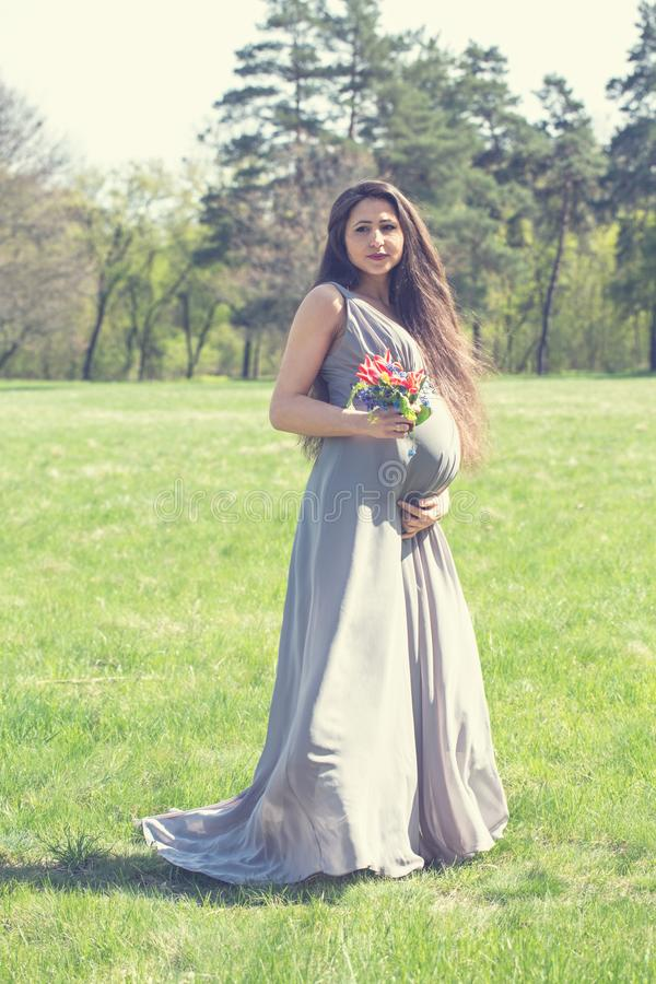 Pregnant woman with a bouquet royalty free stock photography