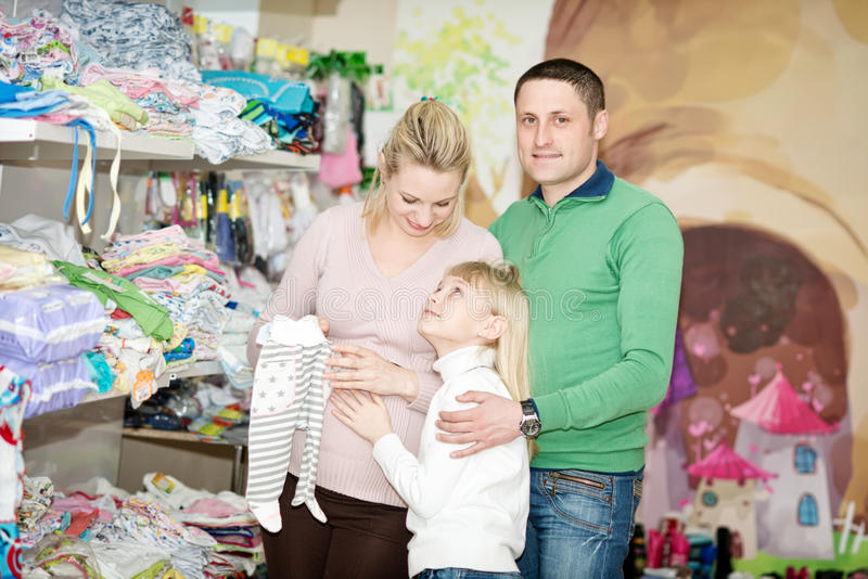 Pregnant woman buying baby clothes in supermarket. Pregnant women buying baby clothes in supermarket . Young pregnant women choosing newborn clothes royalty free stock image