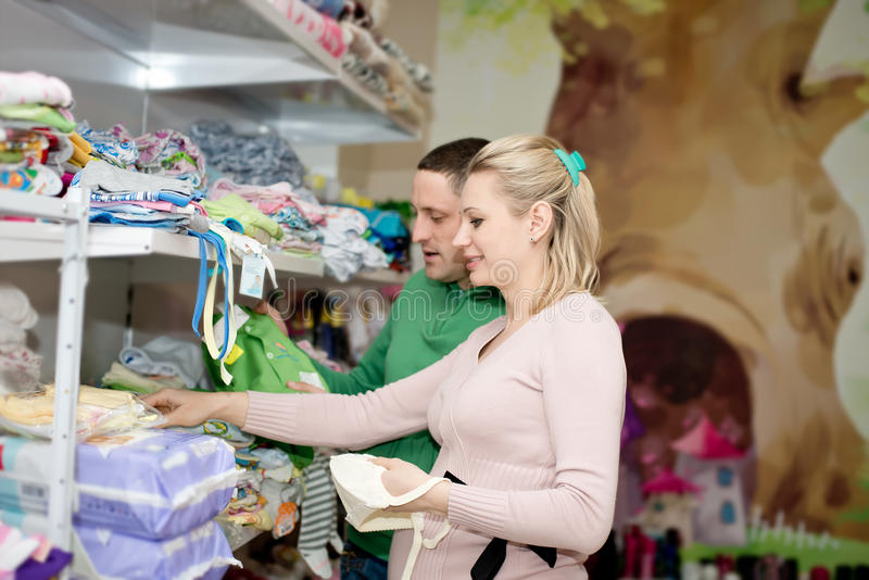 Pregnant woman buying baby clothes in supermarket. Pregnant women buying baby clothes in supermarket . Young pregnant women choosing newborn clothes royalty free stock photography