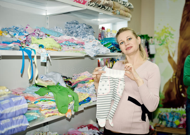 Pregnant woman buying baby clothes in supermarket. Young pregnant woman choosing newborn clothes stock photography