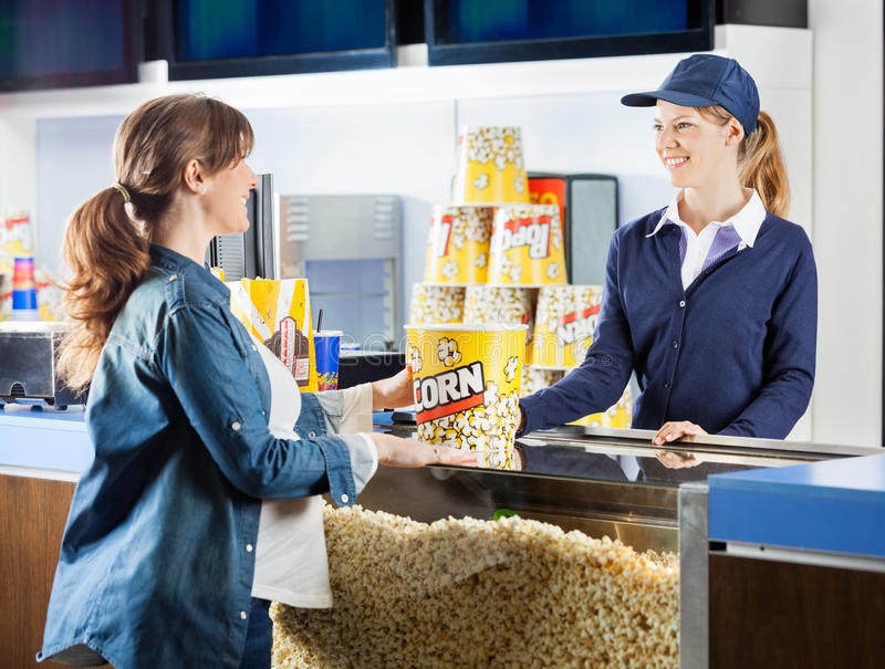 Pregnant Woman Buying Popcorn At Cinema Concession. Mid adult pregnant women buying popcorn from seller at cinema concession stand stock photography