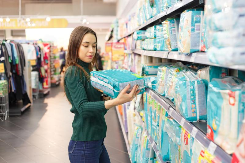 Pregnant woman buys diapers at the supermarket, portrait of young happy mother in shop mall.  royalty free stock images
