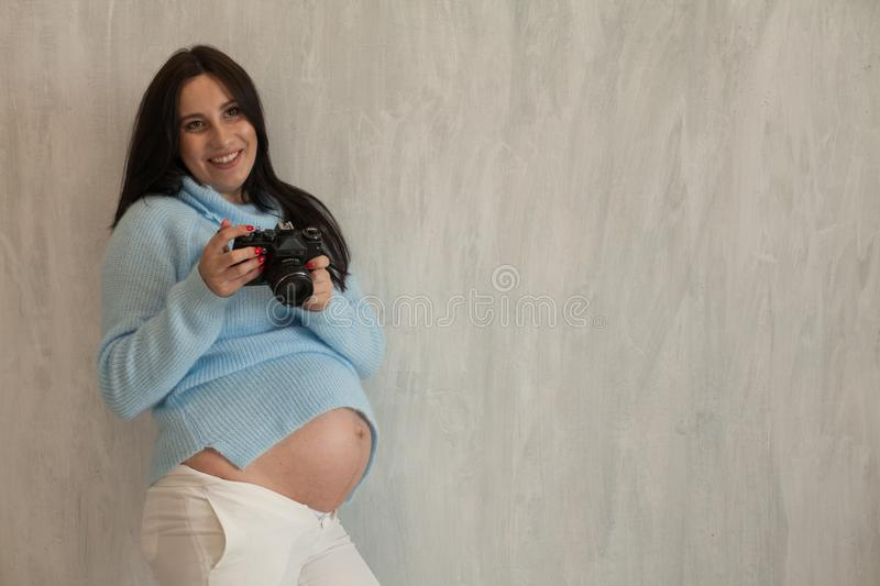 A pregnant woman with a camera brunette portrait genera nice stock images