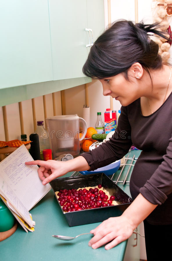 Pregnant woman cooking. A brunette pregnant woman cooking at home. Baking cake in the kitchen stock image