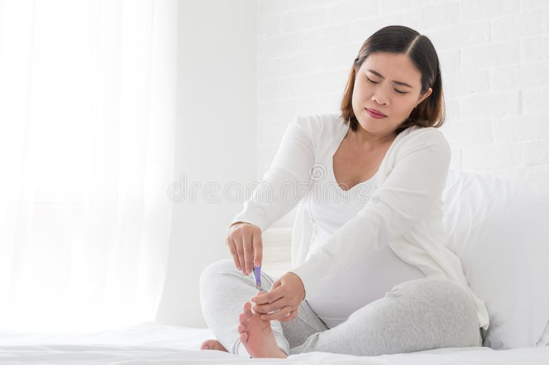 Pregnant woman cutting nails feet by nail clipper stock photos