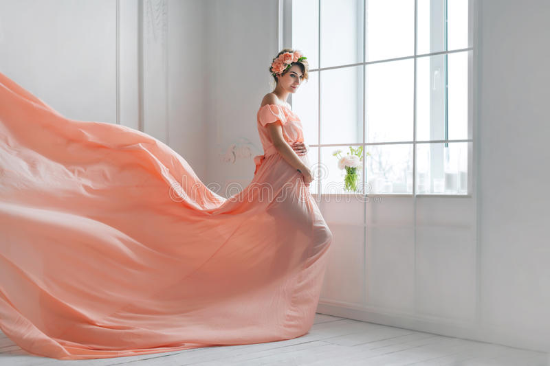Pregnant woman dancing in pink evening dress flying on wind. Waving fabric, fashion shot. stock images