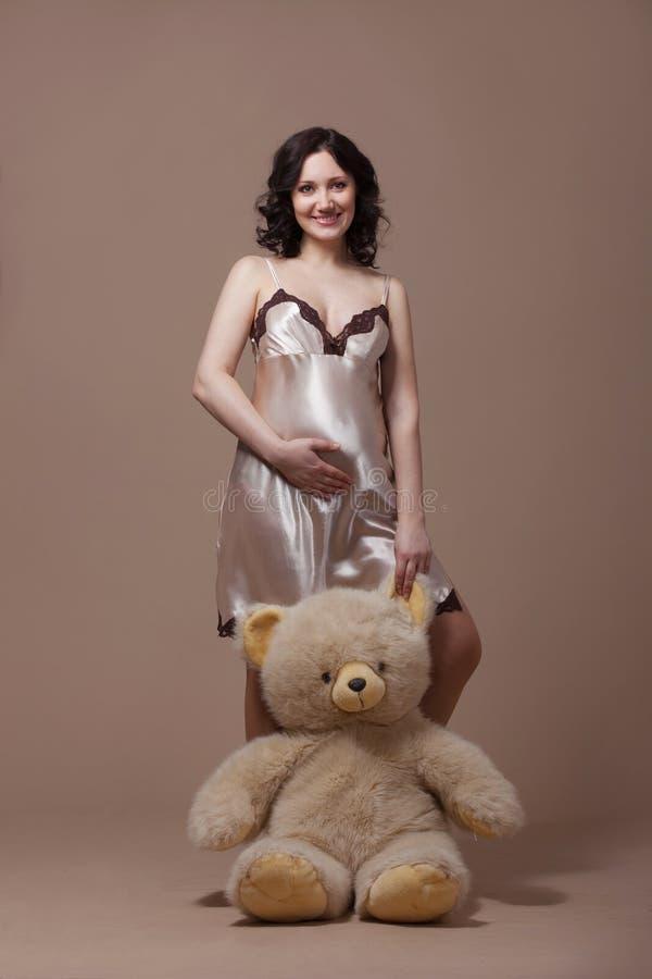 Pregnant woman on dark background stock photos