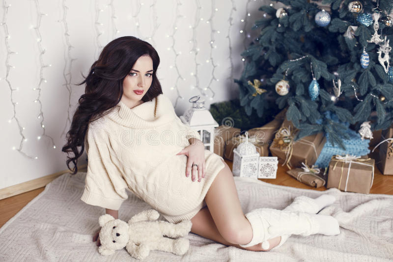 Pregnant woman with dark hair posing beside a Christmas tree. Fashion interior photo of beautiful pregnant woman with dark hair wearing cardigan, posing beside a stock photo