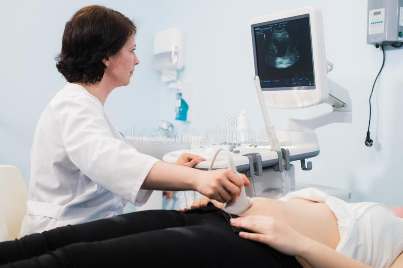 Pregnant woman and doctor hands with ultrasound equipment. Pregnant women and doctor hands with ultrasound equipment stock photos