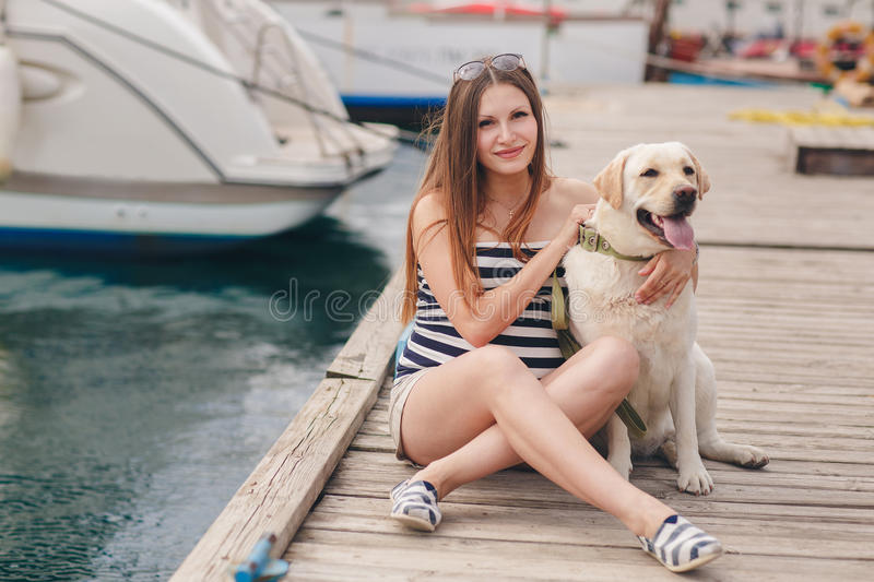 A pregnant woman with a dog on the dock. Beautiful young pregnant woman,a brunette with long straight hair and brown eyes,wears a gold neck chain and cross,sits stock photos