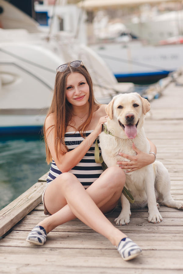 A pregnant woman with a dog on the dock. Beautiful young pregnant woman,a brunette with long straight hair and brown eyes,wears a gold neck chain and cross,sits stock photography