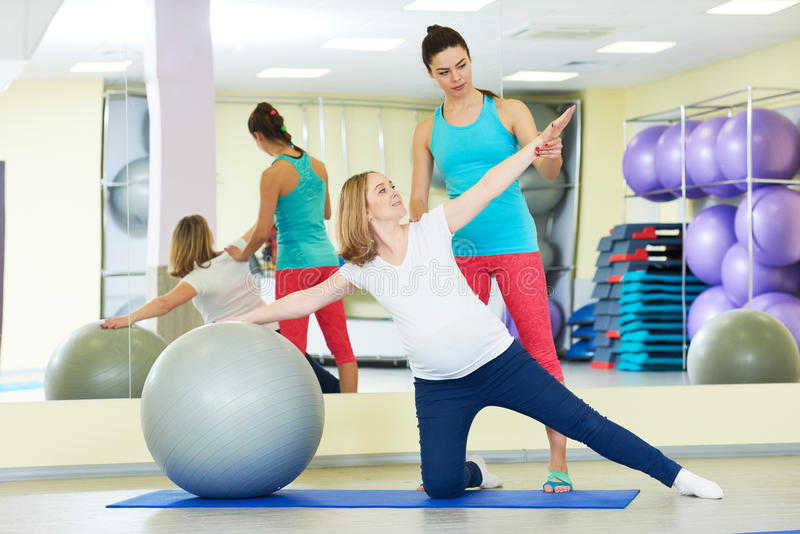 Pregnant woman doing fitness ball exercise with coach. Young pregnant women doing fitness ball exercise with female instructor in sport club royalty free stock images