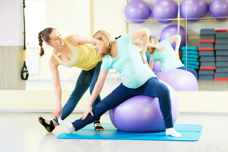Pregnant woman doing fitness ball exercise with coach. Young pregnant women doing fitness ball exercise with female instructor in sport club stock photo