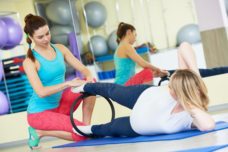 Pregnant woman doing fitness exercise with coach stock photo