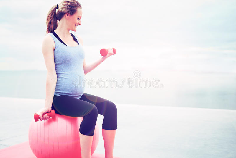 Pregnant woman doing fitness exercises stock photo
