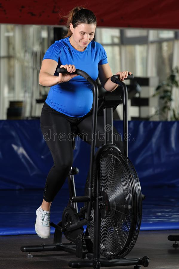 Pregnant woman doing intense workout at gym air bike stock photography