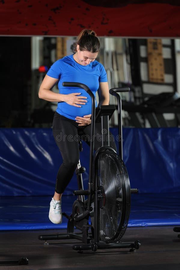Pregnant woman doing intense workout at gym air bike stock image