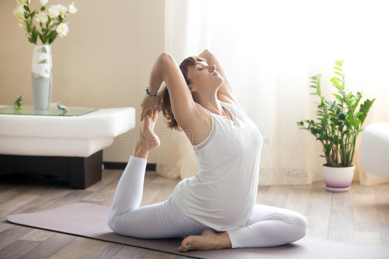 Pregnant woman doing one-legged pigeon yoga pose at home stock photos
