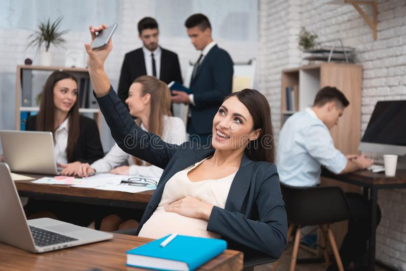 Pregnant woman doing selfie on phone in office. Pregnant woman with working team. royalty free stock image