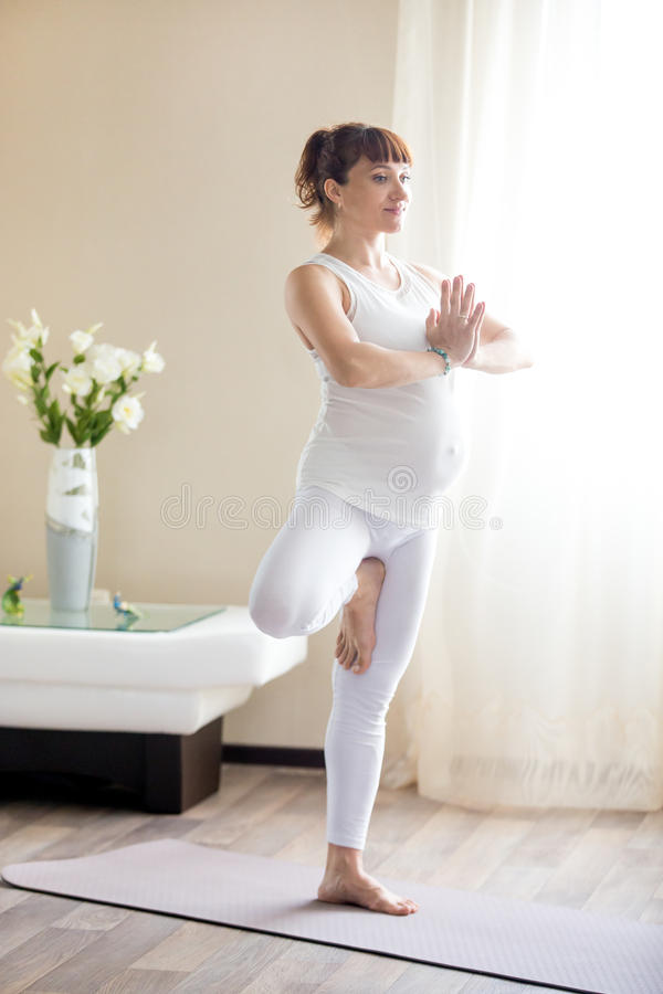 Pregnant woman doing Tree yoga pose at home royalty free stock photos