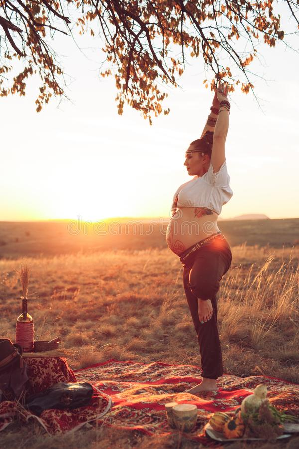 Pregnant woman doing yoga in the field at sunset. Girl holding a dream catcher and doing exercise.  stock image
