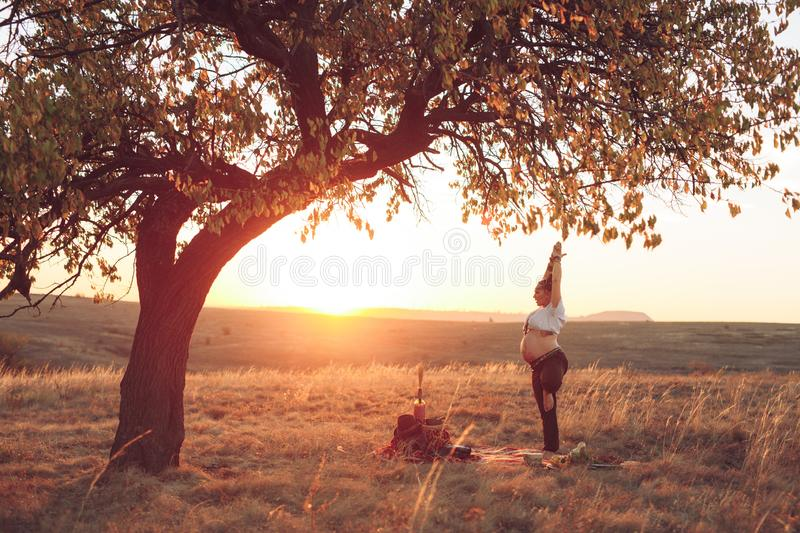 Pregnant woman doing yoga in the field at sunset. Girl holding a dream catcher and doing exercise.  royalty free stock photos