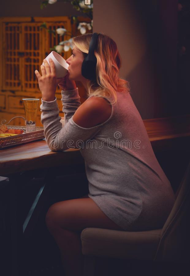 Pregnant woman drinking a tea and listenig music at home. Young attractive relaxed pregnant woman drinking tea and enjoying listening music in headphones royalty free stock photos