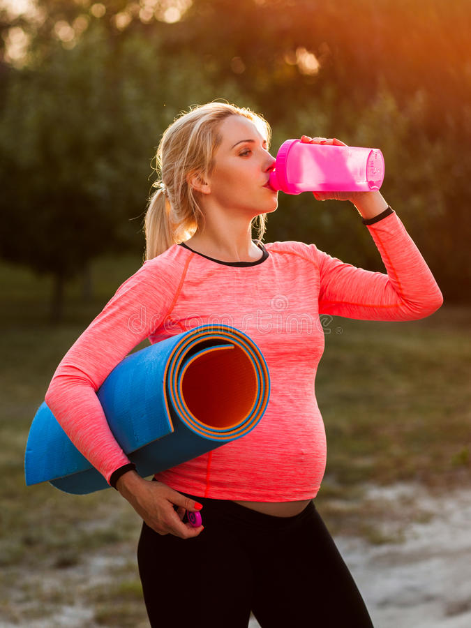 Pregnant woman drinking water after fitness royalty free stock photos