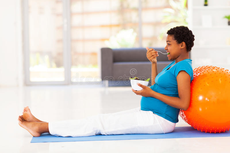 Pregnant woman eating. Pregnant african american woman eating healthy salad on exercise mat