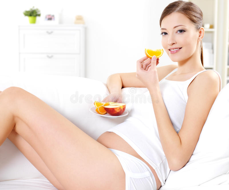 Pregnant woman eating fresh fruits royalty free stock images