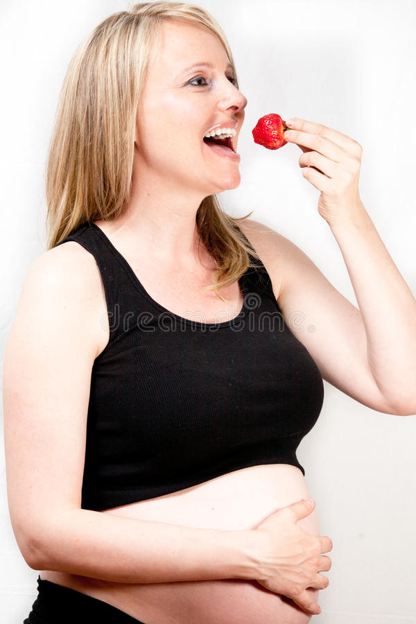 Pregnant Woman Eating strawberry stock photo