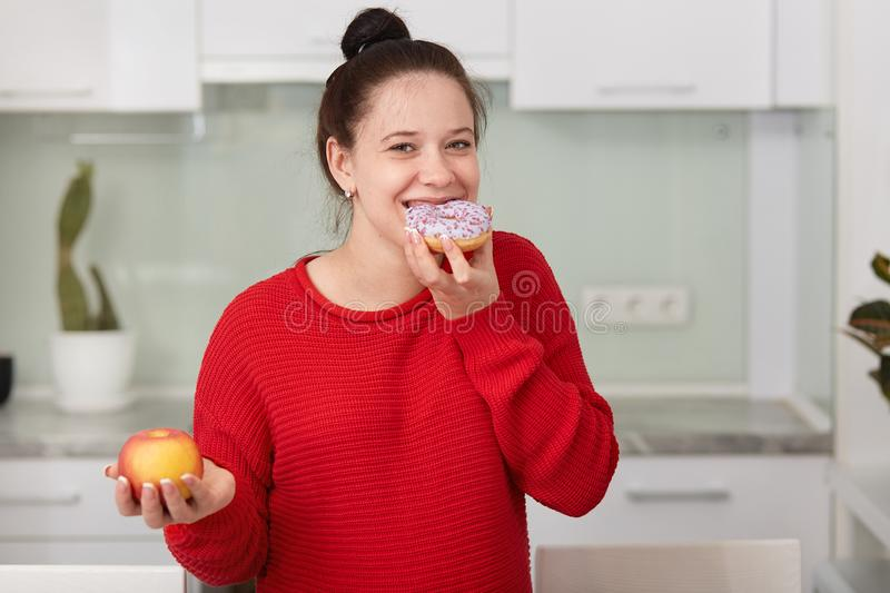 Pregnant woman eating sweet cake and holding apple in another hand, stands wearing red casual sweater in front white kitchen. Interior, female expresses stock photos